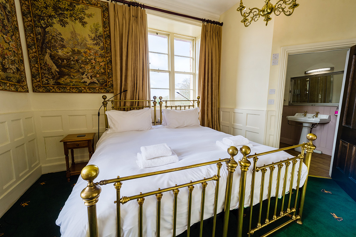 Large brass bed and decorative wall coverings in the Hothfield bedroom at Appleby Castle
