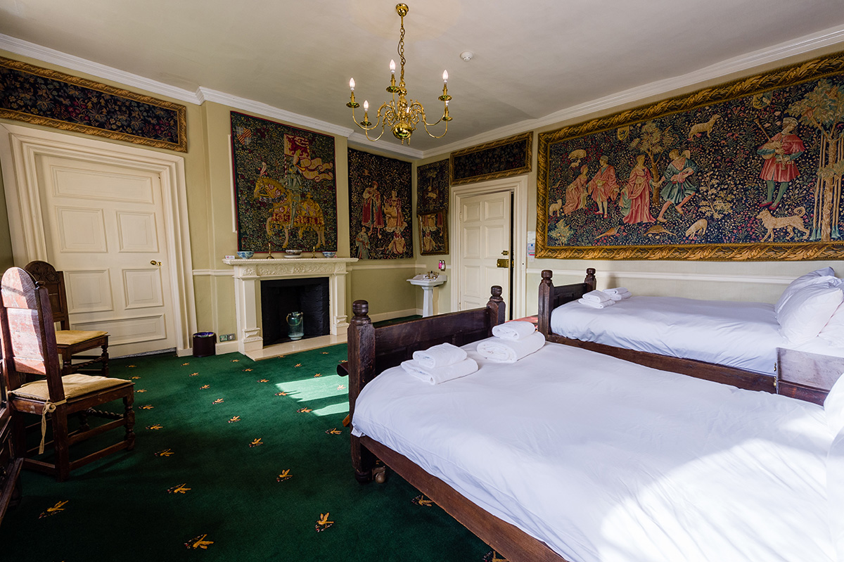 Decorative wall coverings and antique twin beds in the Tufton bedroom at Appleby Castle