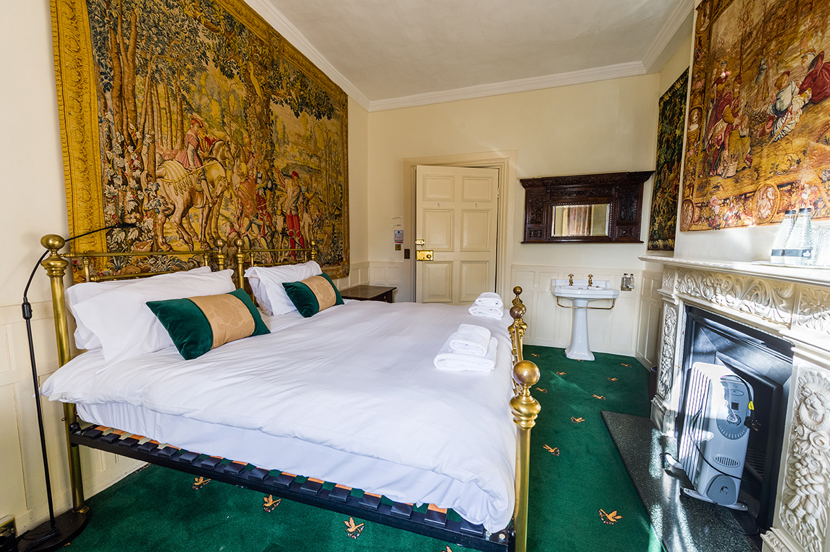 Large brass bed and decorative wall coverings in the Thanet bedroom at Appleby Castle