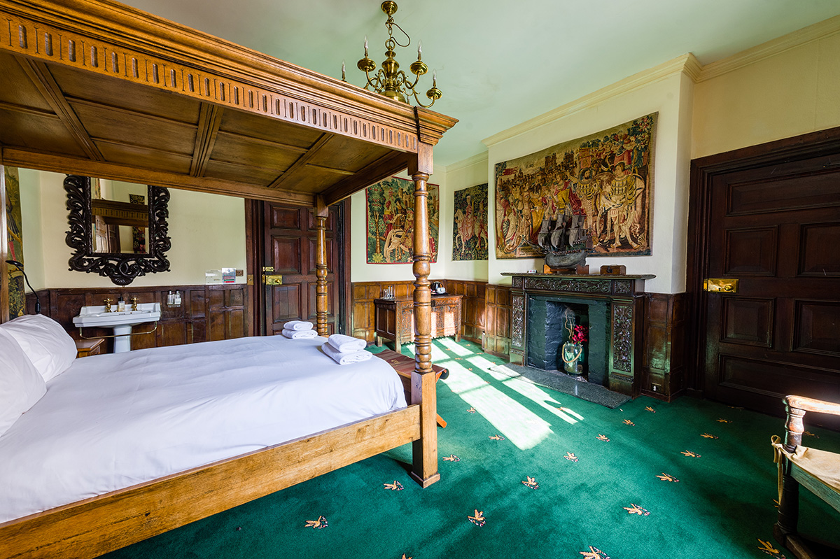 Four poster antique bed and antique wall coverings in the Vipont bedroom at Appleby Castle