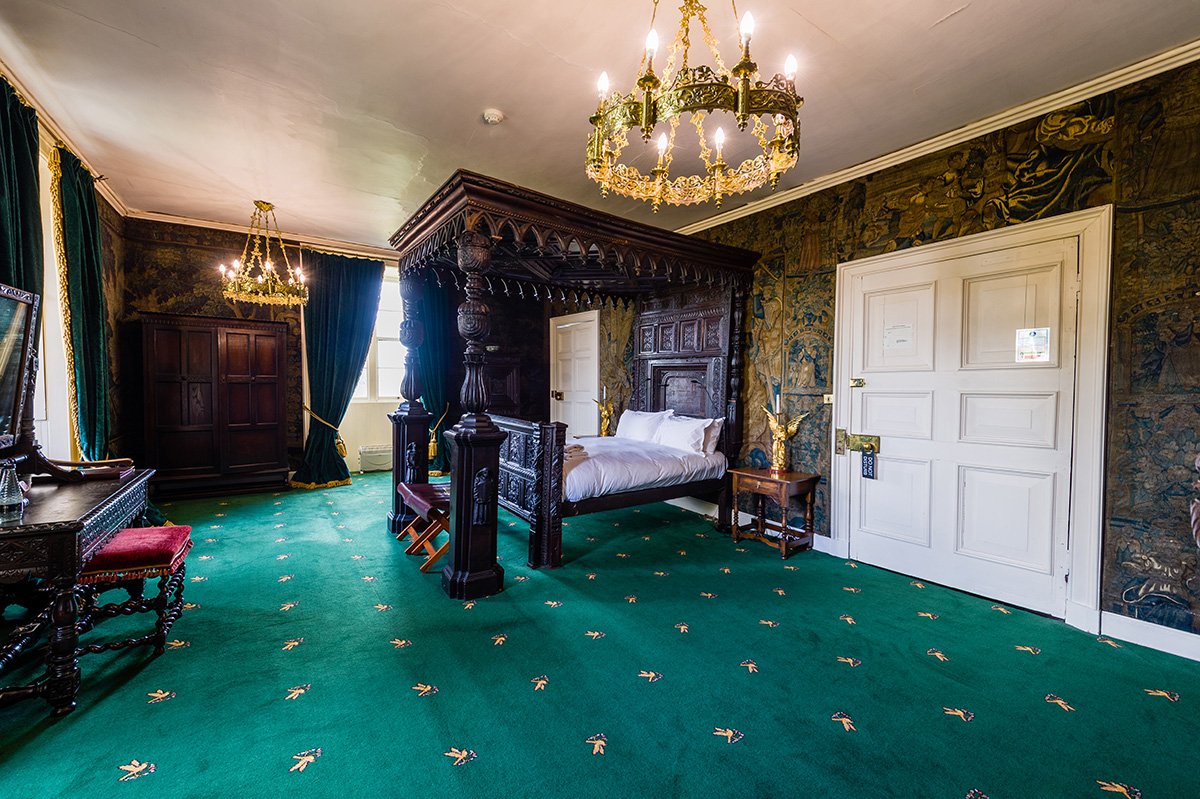 Large four poster bed and antique wall coverings in the State bedroom at Appleby Castle