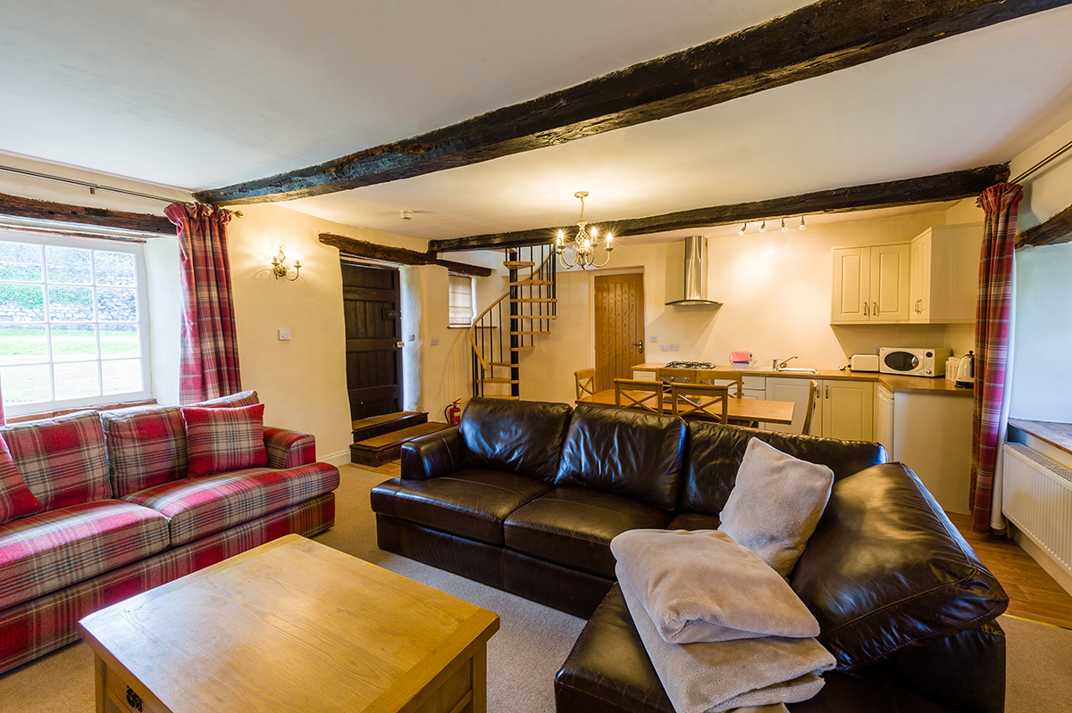 Sofas, dining table and kitchen in Lady Anne's Cottage at Appleby Castle