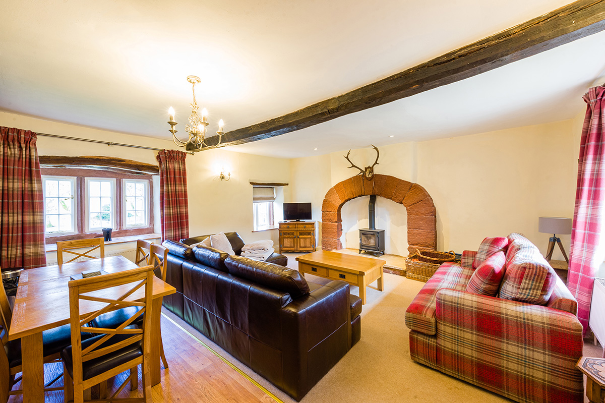 Lounge, log burner and dining table in Lady Anne's Cottage at Appleby Castle