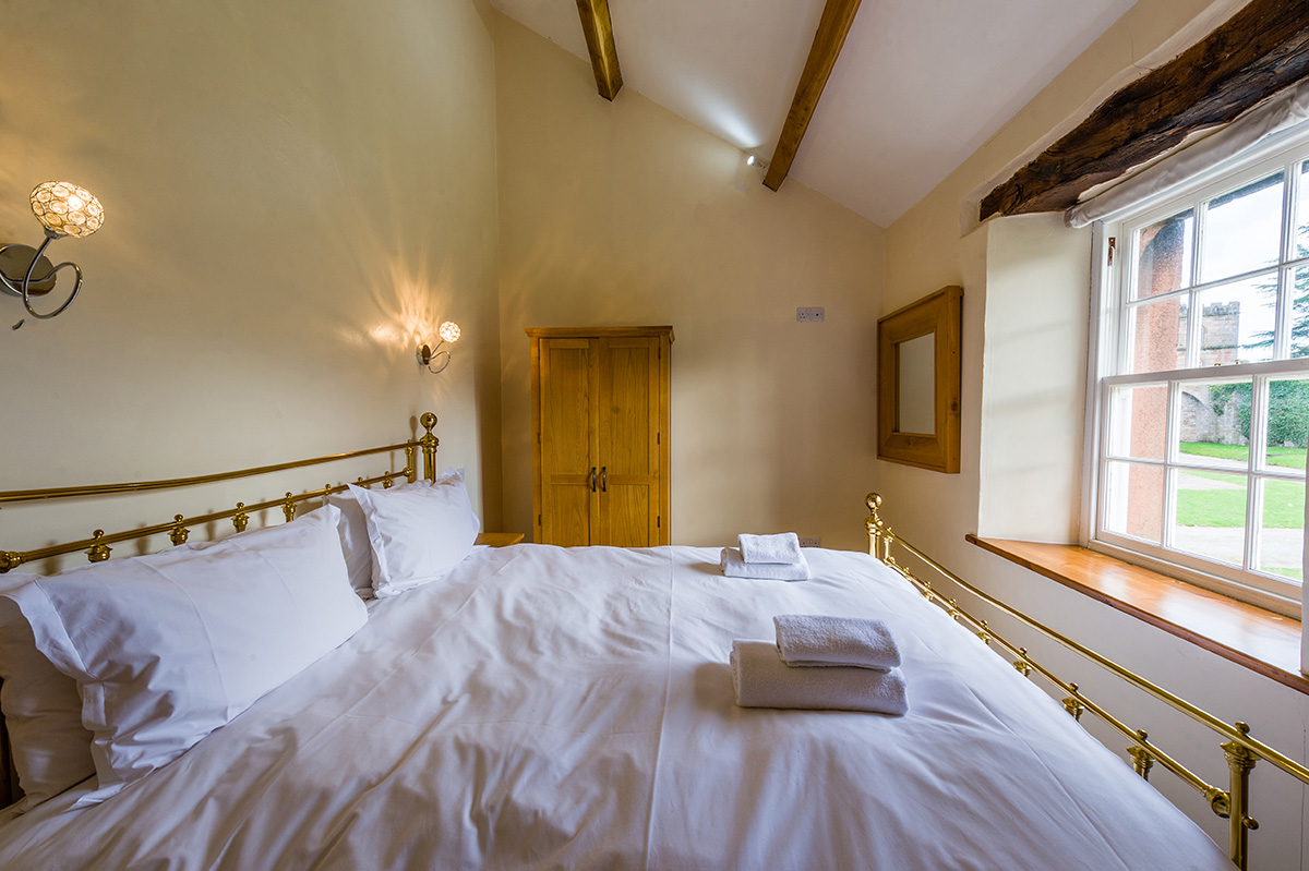 Large brass bed in the self-contained holiday cottage at Appleby Castle in Cumbria