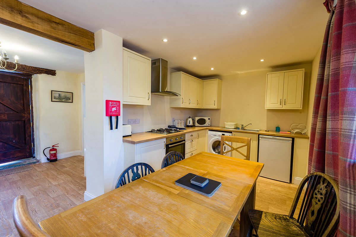 Dining table and kitchen in the self-contained holiday cottages at Appleby Castle