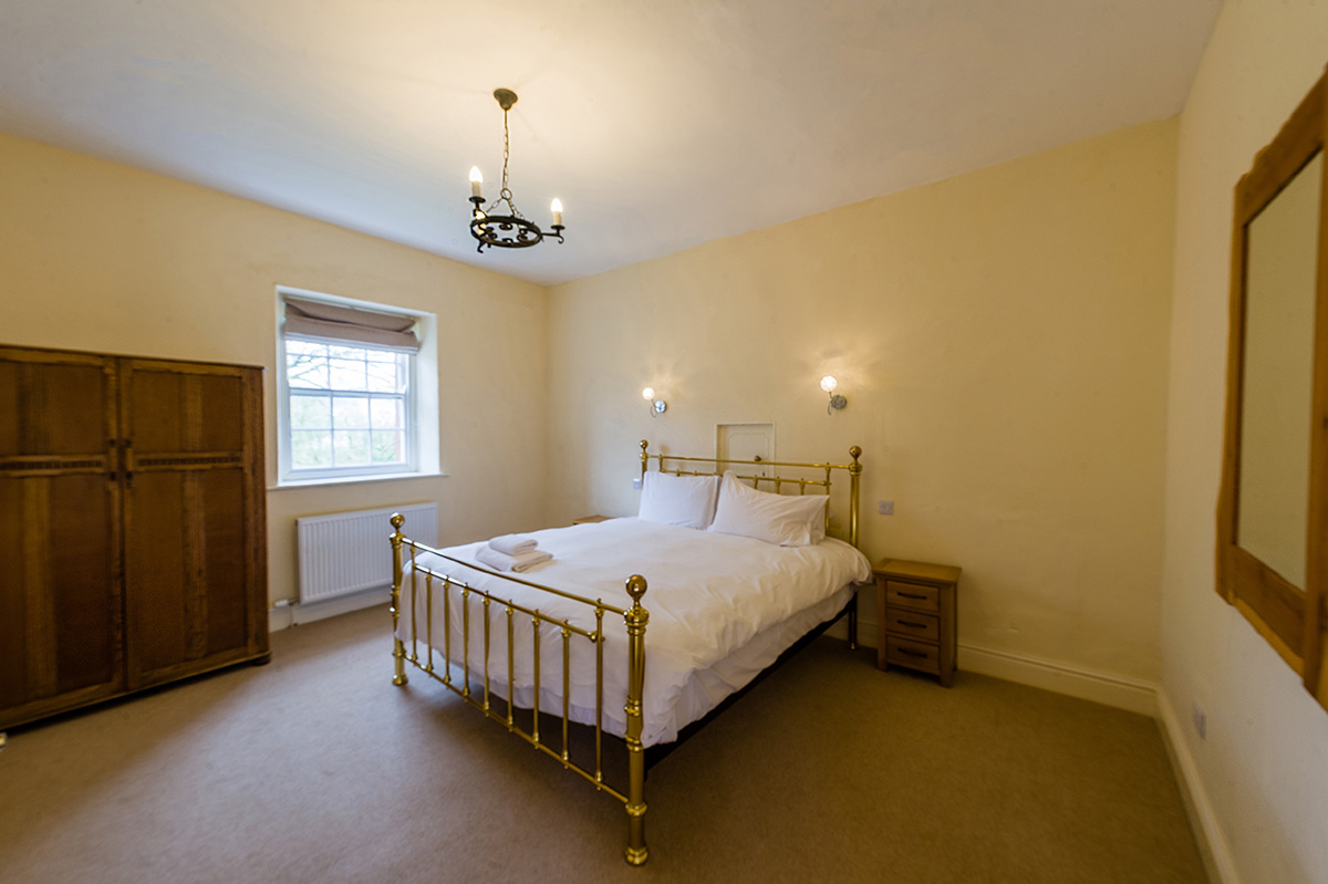 Large brass bed in the self-contained holiday accommodation in Cumbria