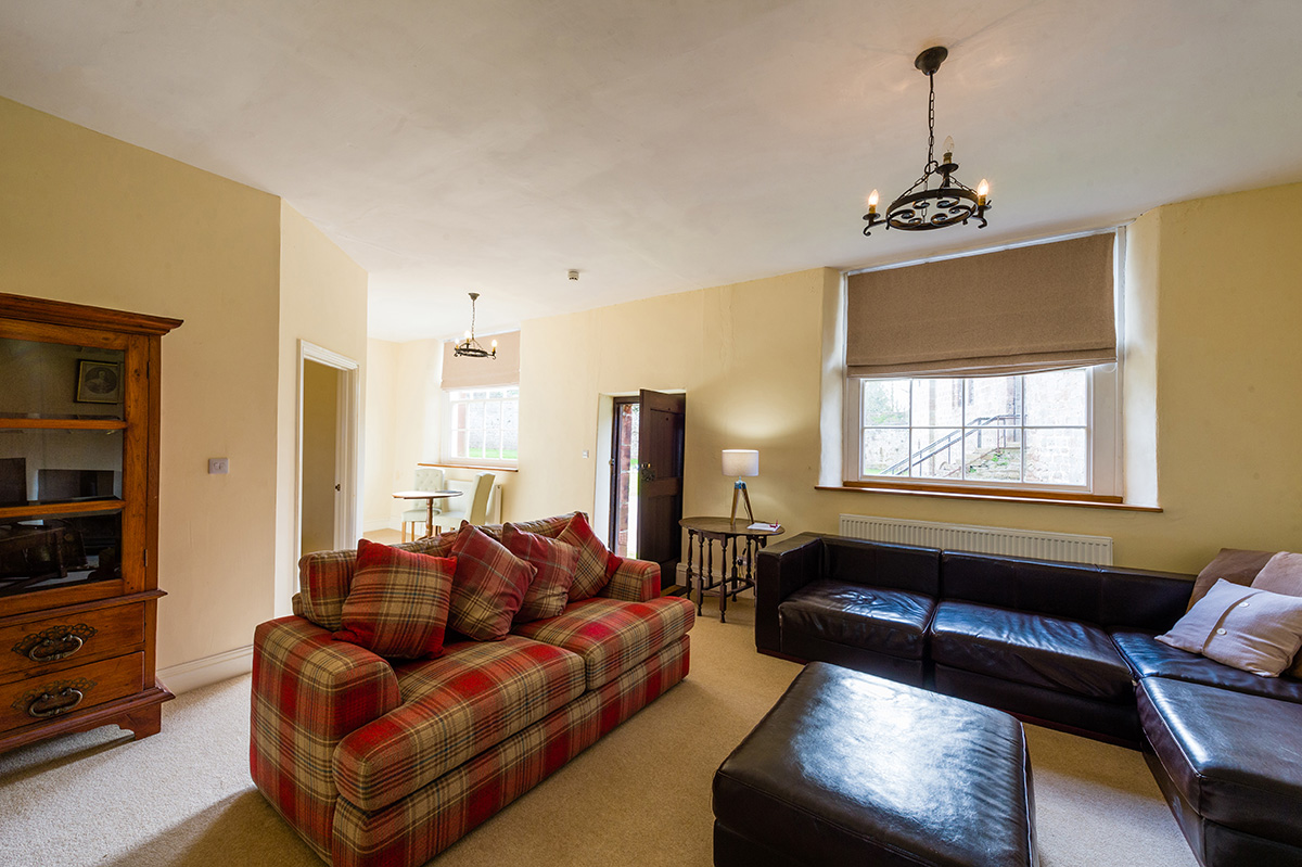 Large comfortable sofas in the lounge in the l self-contained holiday cottages at Appleby Castle